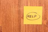 Help written on sticker on wooden background — Stock Photo