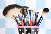 Makeup brushes in a black polka-dot cup on colorful background close-up — Stock Photo