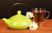 Théière et tasse à thé à la camomille sur table en bois sur fond marron — Photo