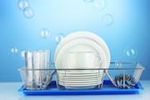 Clean dishes on stand on blue background — Stock Photo