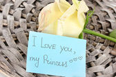 Beautiful rose on wicker mat with card close-up — Stock Photo