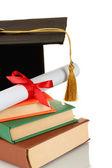 Grad hat e diploma con libri isolato su bianco — Foto Stock