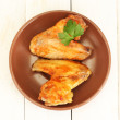 Roasted chicken wings with parsley in the plate on white wooden background close-up — Stock Photo #12142465