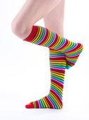 Vrouwelijke benen in kleurrijke gestreepte sokken geïsoleerd op wit — Stockfoto