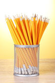 Lead pencils in metal cup on wooden table on yellow background — Stock Photo