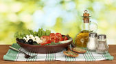 Tasty greek salad on bright green background — Stock Photo