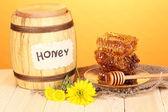 Baril de miel et nid d'abeille sur une table en bois sur fond orange — Photo