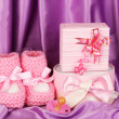 Pink baby boots, pacifier, gifts on silk background — Stock Photo #12159575