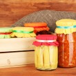 Jars with canned vegetables on wooden background close-up — Stock Photo #12159648