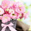 Stock Photo: Bouquet of eustoma flowers in wicker vase, on wooden table, on green background