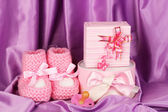 Pink baby boots, pacifier, gifts on silk background — Stock Photo