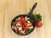 Frying pan with vegetables on wooden background — Stock Photo