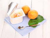 Yogurt with apricot on wooden background — Stock Photo