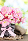 Bouquet of eustoma flowers in wicker vase, on wooden table, on green background — Stock Photo