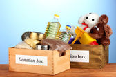 Donation box with food and children's toys on blue background close-up — Stock Photo