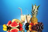 Milk shakes with fruit on blue background close-up — Stock Photo