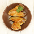 Roasted chicken wings with parsley in the plate on white wooden background close-up — Stock Photo #12160677
