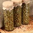 Glass jars with tinned capers on sack background close-up — Stock Photo #12161323