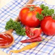 Ketchup and ripe tomatoes on wooden table — Stock Photo