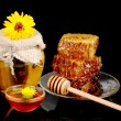 Jar of honey and honeycomb on black background - Stock Photo
