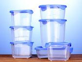 Recipientes de plástico para o alimento na mesa de madeira no fundo azul — Foto Stock