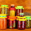 Jars with canned vegetables and fruit on wooden background close-up - Zdjęcie stockowe