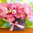 Bouquet of eustoma flowers in wicker vase, on wooden table, on green background — Stock Photo #12182532