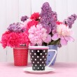 Spring flowers and cup on table on white wooden background — Stock Photo