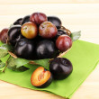 Rip plums on basket on wooden table — Stock Photo #12184376