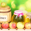 Honey and apples with cinnamon on wooden table on natural background - Stock Photo