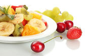 Fresh fruits salad on plate and berries isolated on white — Stock Photo