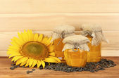 Sunflower oil and sunflower on wood background — Photo