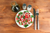 Salad with capers in the plate on wooden background — Stock Photo