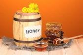 Sud medu a plástve na dřevěný stůl na oranžovém pozadí — Stock fotografie