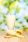 Banana milk shake on wooden table on bright background — Stock Photo