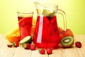 Sangria sklenice a sklo s ovocem, na dřevěný stůl, na zeleném pozadí — Stock fotografie