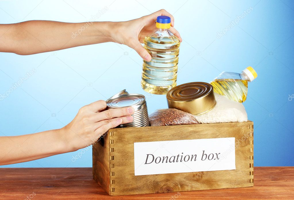Donation box with food on blue background close-up — Stock Photo #12182550