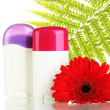 Stock Photo: Deodorants with flower and green leaf isolated on white
