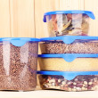Filled plastic containers on wooden background - Zdjęcie stockowe