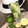 Mojito and a hat on a gray wooden background — Stock Photo