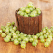Green gooseberry in wooden cup on wooden background — Stock Photo #12191463
