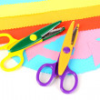 Colorful zigzag scissors with color paper isolated on white — Stock Photo #12191539