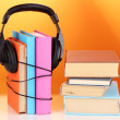 Headphones on books on orange background — Foto Stock