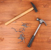 Hammers and metal nails on wooden background — Stock Photo