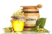 Jar and barrel with linden honey and flowers isolated on white — Stock Photo