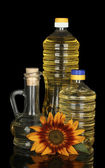 Sunflower oil in a plastic bottles and small decanter isolated on black background — Stock Photo