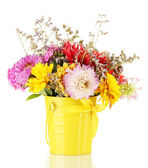 Bright yellow bucket with flowers isolated on white — Stock Photo