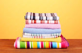 Kitchen towels on wooden table on orange background close-up — Stock Photo
