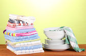 Kitchen towels with dishes on green background close-up — Stock Photo