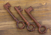 Three antique keys on wooden background — Stock Photo
